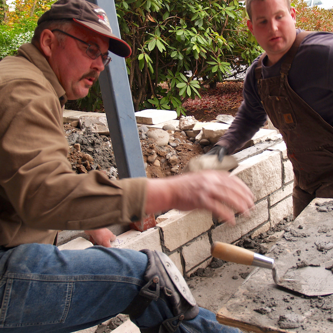Journeyman pointer-caulker-cleaner Mark Roddy, left, works with an apprentice to rebuild a wall outside the Oregon AFL-CIO office.