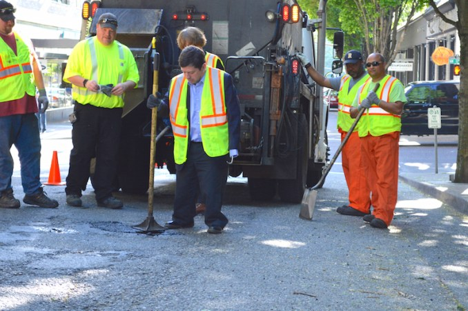 ONE POTHOLE DOWN, AND 7,500 TO GO At left, Steve Novick, the City Commissioner in charge of the Portland Bureau of Transportation (PBOT), helps a street maintenance crew fill a pothole at NW 12th and Everett April 19. Behind him (from left) are Jeff Peterson, Cory Long, Billy Spires, and Mark Bartholomew, members of Laborers Local 483 (and manager Suzanne Kahn directly behind). PBOT crews have filled over 7,500 potholes in the last year.