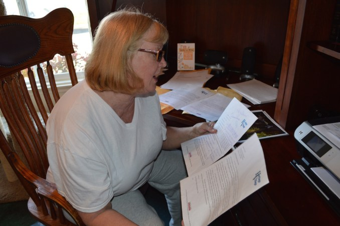 Heritage Village resident Diane Bareno looks over demand letters she's received from Cal-Am Properties.