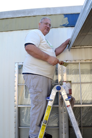 Applying exterior paint is Machinists Lodge 1005 vice president Mike McLaren, a 22-year Daimler truck employee who's currently on his seventh layoff at the Portland truck plant.