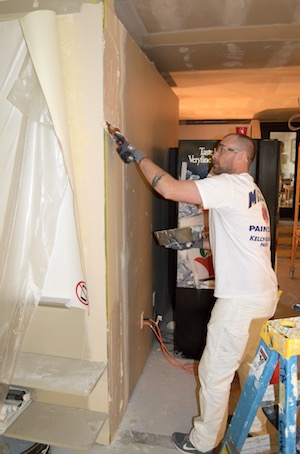 David Adams, a Level III drywall fin- isher apprentice and member of Lo- cal 10, applies a first coat of mud. Adams works for Western Partitions.