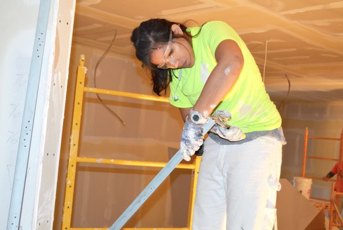 Patricia Gadd, a Level II drywall finisher apprentice and member of Painters and Drywall Finishers Local 10, cuts a metal corner. Gadd works for Harver Company.
