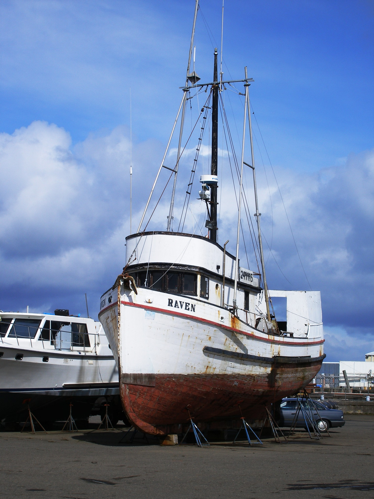 The Raven, a wooden fishing vessel, sits approximating her water-borne stance on blocks, the car in the background gives a little perspective for size