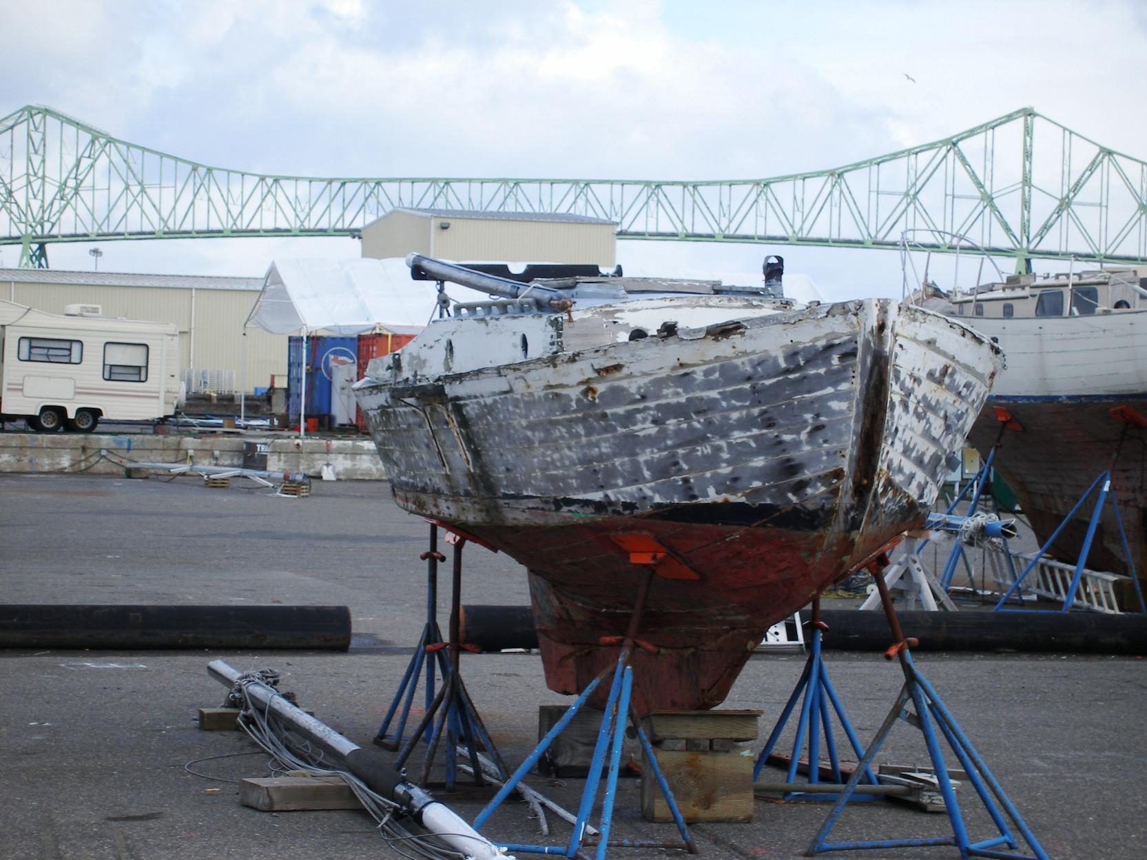 A sailboat hull sits up on blocks, the Astoria-Megler bridge is backdrop