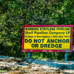 USA: Louisiana, the Atchafalaya Basin, with C. C. Lockwood, Atchafalaya River bank signage for ethylene gas pipeline