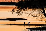 USA: Louisiana, St Francisville, two fishermen at sunset with fishing poles on banks of Mississippi River seen from banks of Bayou Sara
