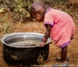 Kenya: Amboseli, Maasai (aka Masai) child looking into water bucket,