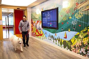 Clio employee walking white dog in lobby