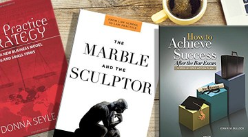 The three featured books on a desk