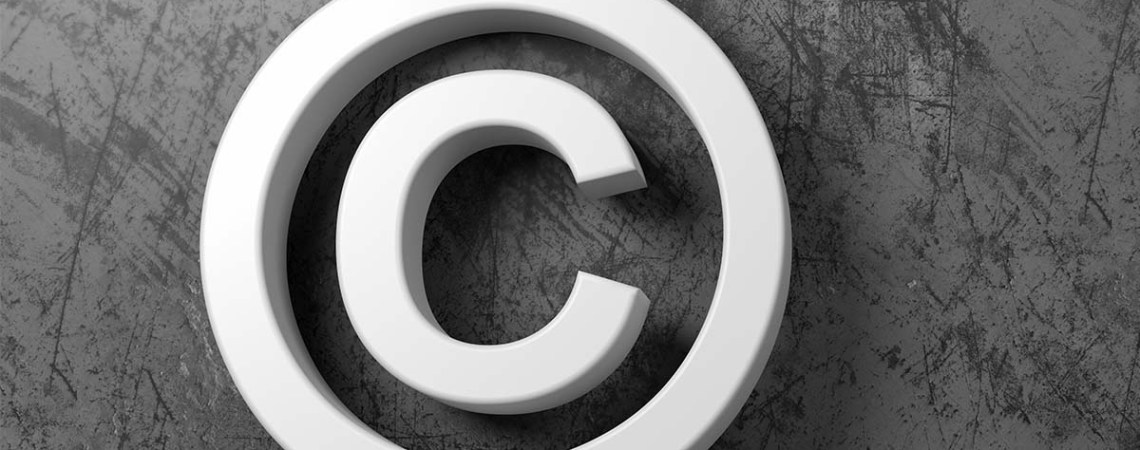 White copyright symbol on wooden floor against a grey wall with