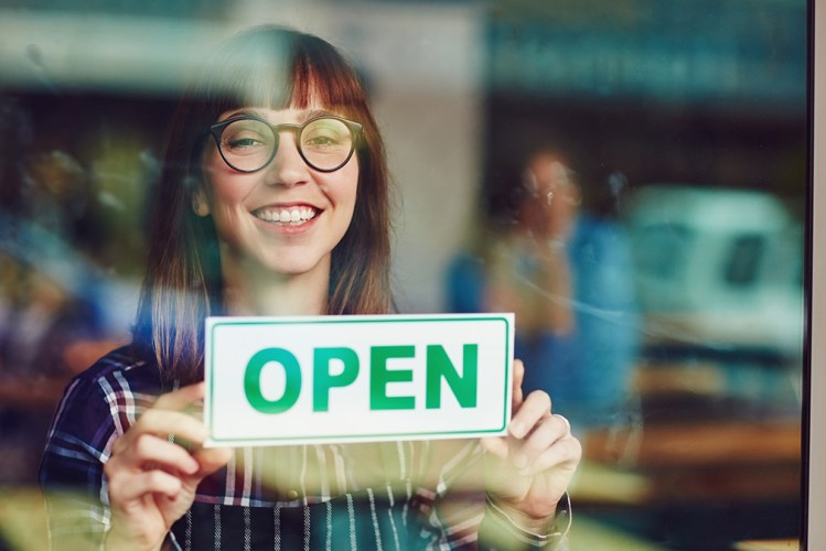 Young female attorney hanging open sign on the door or her new law office