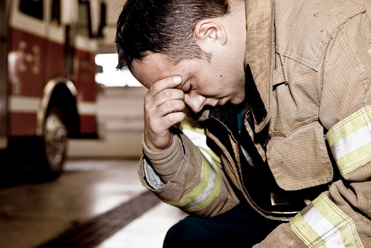 Exhausted firefighter rests with hand over head.