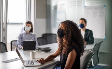 Image of three people sitting at a conference room table, all wearing masks.