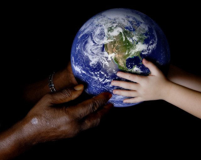 Black and white hands holding a globe