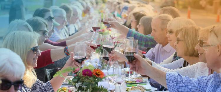 Digitally altered image of many people sitting at a long table. The people have raised glasses of wine to toast.