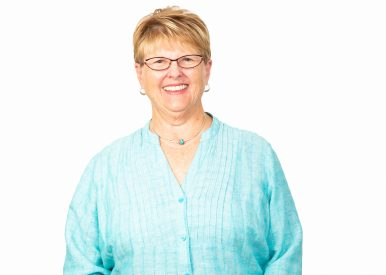 Image of Ellen Mason. An older caucasian woman with short blonde hair smiles at the camera. She wears glasses and a light blue blouse.