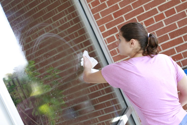 A woman in a pink shirt wipes a cloth against a window.