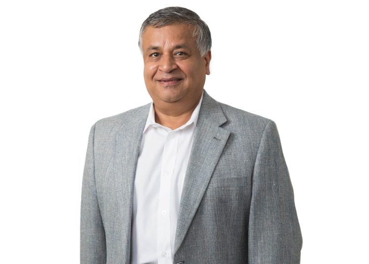 Image of Samir Javeri. An older Indian man smiles at the camera. He is wearing a white button down shirt, with a gray suit jacket and blue slacks.