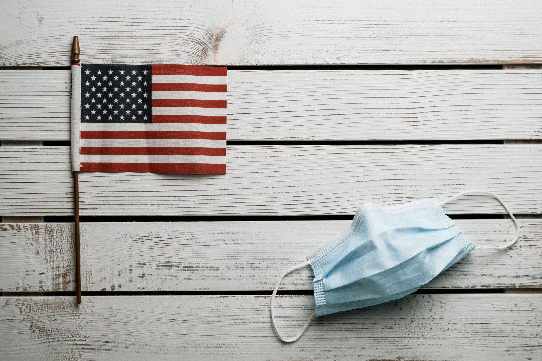 american flag and disposable mask on wooden table