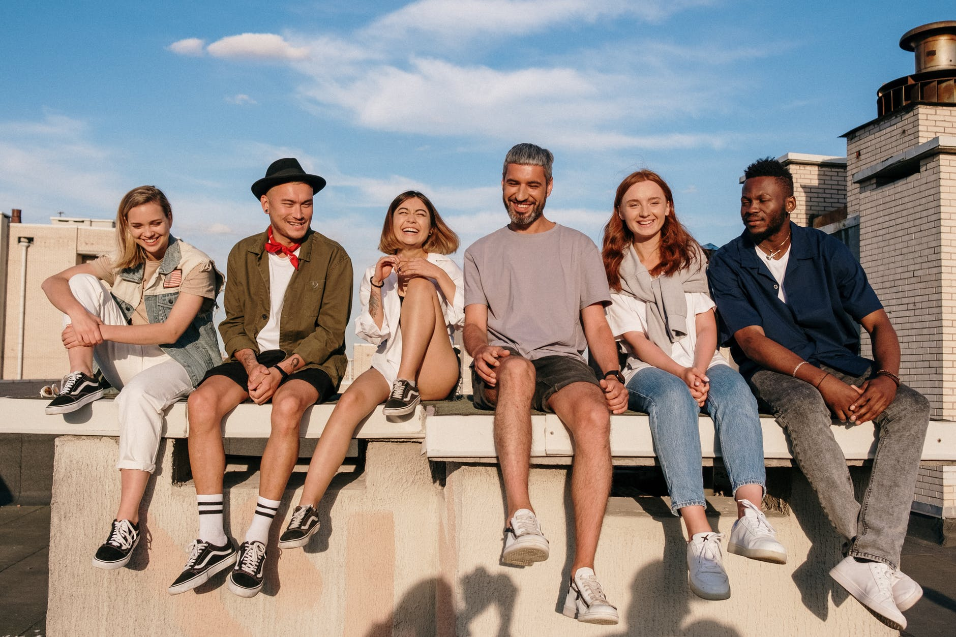 group of people sitting on concrete bench