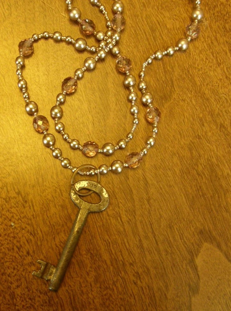 beaded necklace with light pink, iridescent, and silverish beads and antique skeleton key