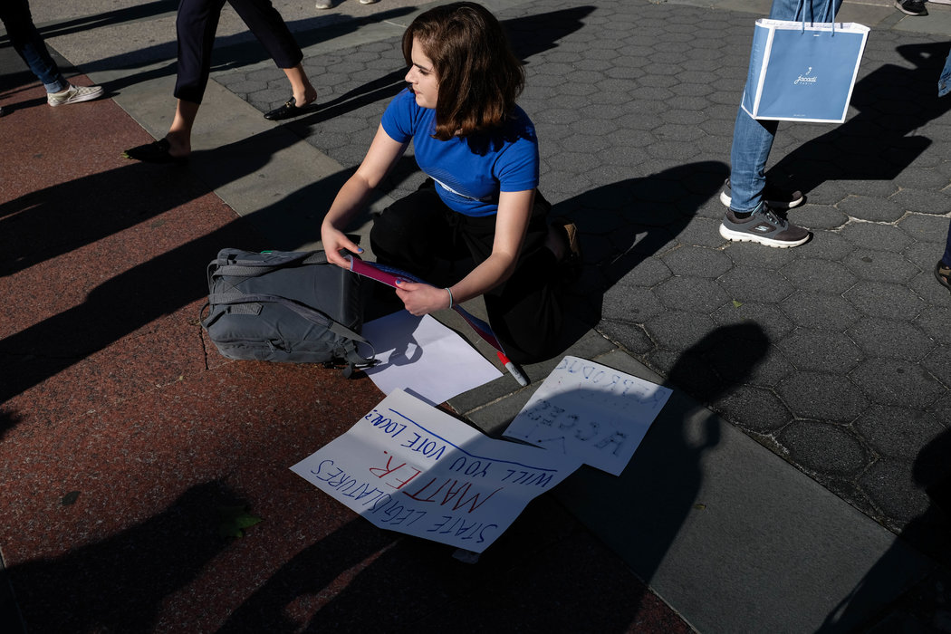 A young woman creating a poster for the #StopTheBans rally in New York. The protest called attention to legislation restricting access to abortion.
