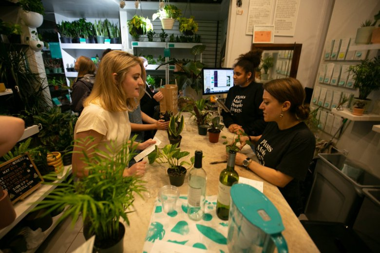 Emily Deevers left, 23, has a few last questions for Elana Frank, 25, after the Plants 101 workshop, as others choose their new potted plants.
