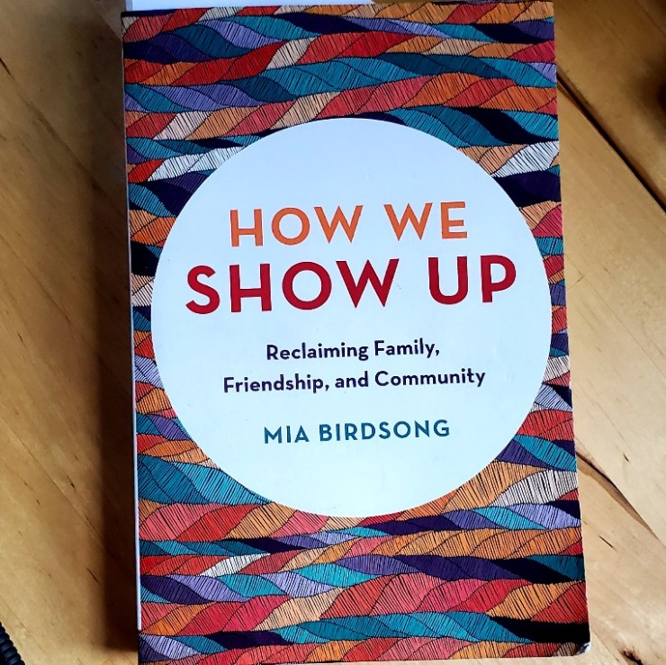 """Cover of """"How We Show Up: Reclaiming Family, Friendship, and Community"""" by Mia Birdsong, with its design of tri-color twisted strands looking like rope waves, on a wooden table."""