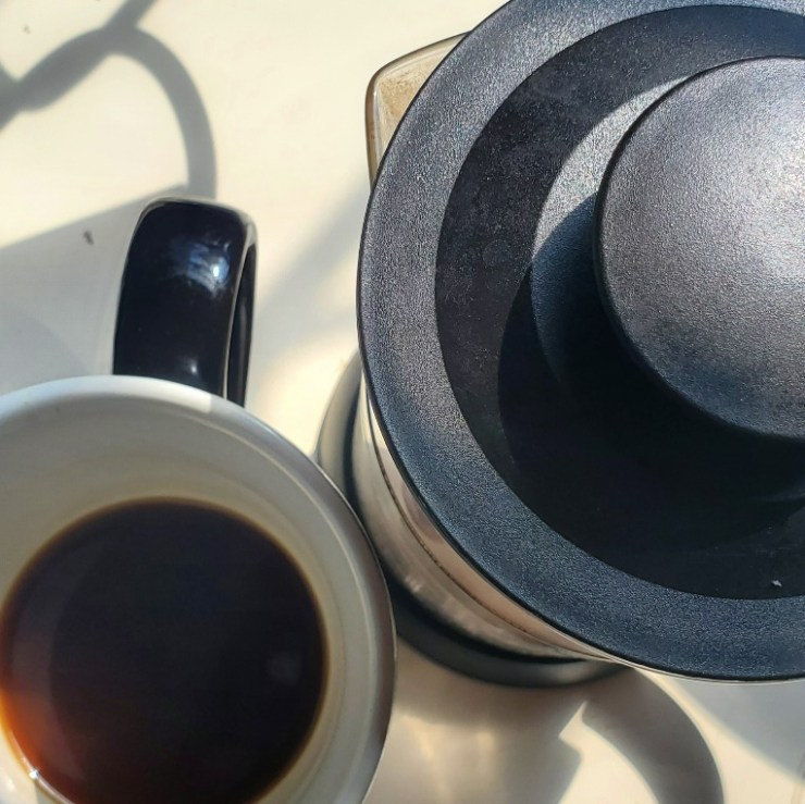 Birds-eye view of a french press and mug with a little coffee left.