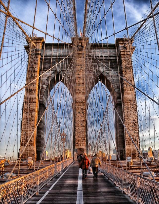 People walking across Brooklyn Bridge