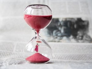 An hourglass with red sand in it