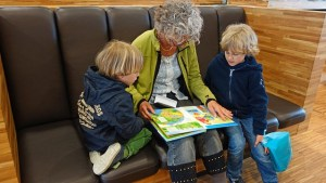Elderly lady reads to her grandchildren - great way to enjoy retirement in NYC