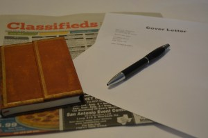 a tabletop with job ads, a notebook and a cover letter