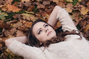 A girl lying in leaves, thinking about moving out of New York.