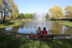 Two college students in New York sitting in front of a lake in the park.