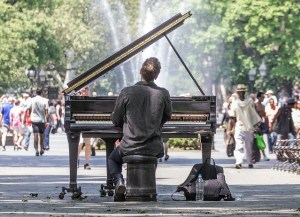 Man playing a grand piano in Central Park.