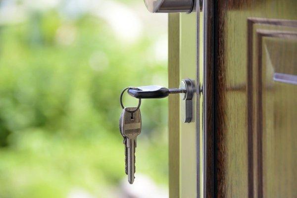 A key in the lock of an open door.