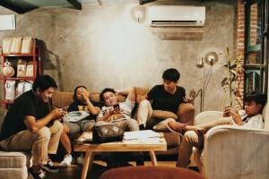 Five young people sitting in their living room, chilling