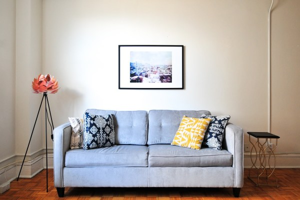 A sofa, a lamp, and a painting on a wall of a living room.