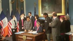 Mayor Bill de Blasio signing legislation into law with Council Member Jumaane Williams standing to his right. Image credit: The Office of Council Member Jumaane Williams