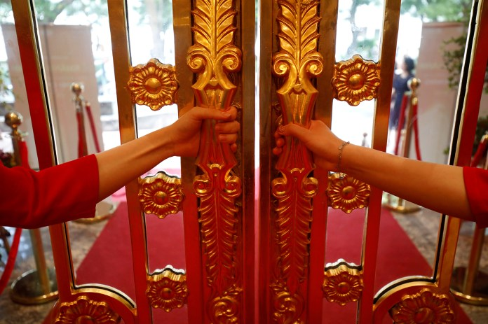 FILE PHOTO: Staff members open the doors of the newly inaugurated Dolce Hanoi Golden Lake luxury hotel, which features gold-plated exteriors and interiors, after the government eased a nationwide lockdown following the global outbreak of the coronavirus d