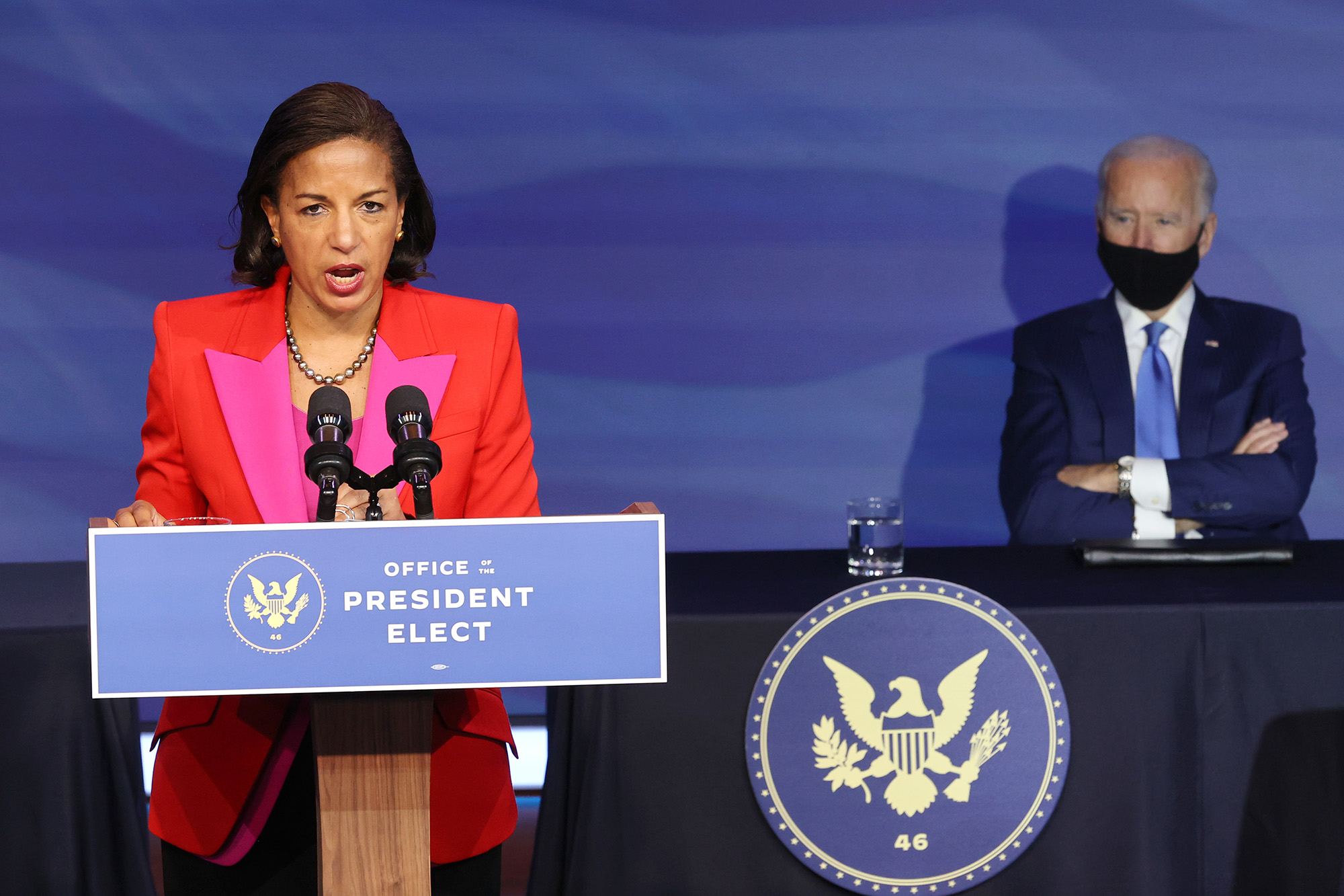 Susan Rice speaking at a podium with Joe Biden in the background