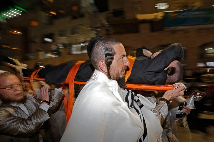 An injured man being carried away from the bleacher collapse at a synagogue in Israel on May 16, 2021.