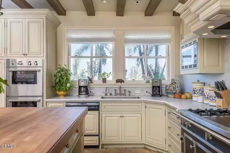 The eat-in kitchen has exposed wooden ceiling beams and cream-colored cabinets.
