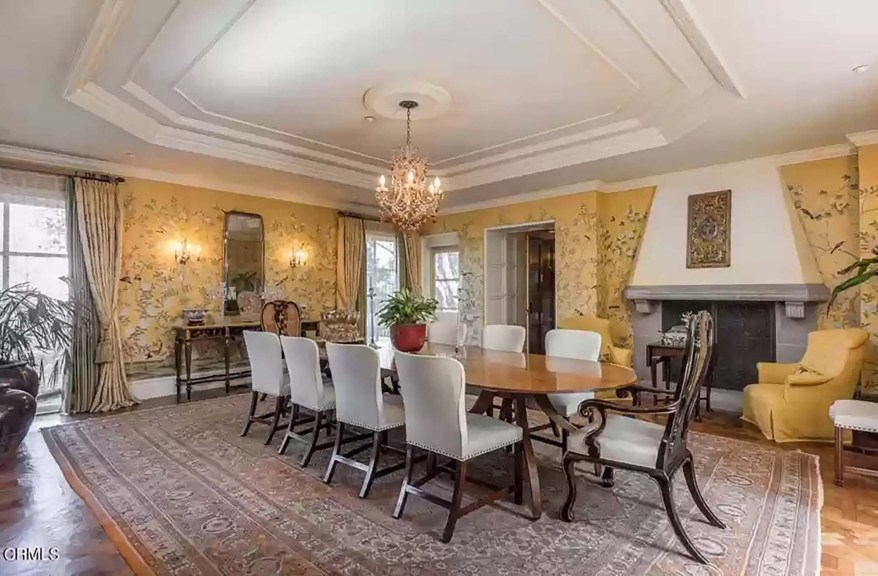 The dining room has yellow silk wallpaper with a floral design.