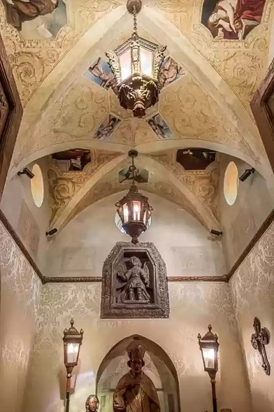 The chapel has an ornate cathedral-style ceiling with stained glass windows and religious paintings on the ceilings.