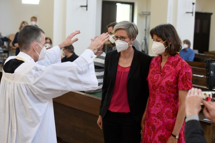 Vicar Wolfgang Rothe, left, blesses the couple Christine Walter, center, and Almut Muenster, right, during a Catholic service with the blessing of same-sex couples in St Benedict's Church in Munich, Sunday, May 9, 2021.