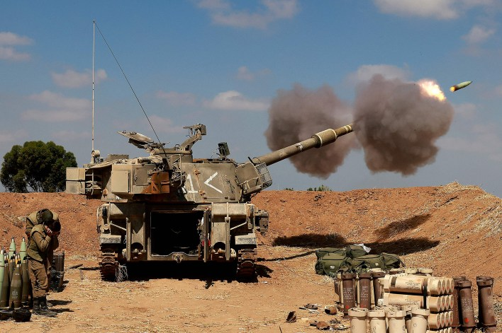 Israeli soldiers fire a 155mm self-propelled howitzer towards the Gaza Strip from their position near the southern Israeli city of Sderot.