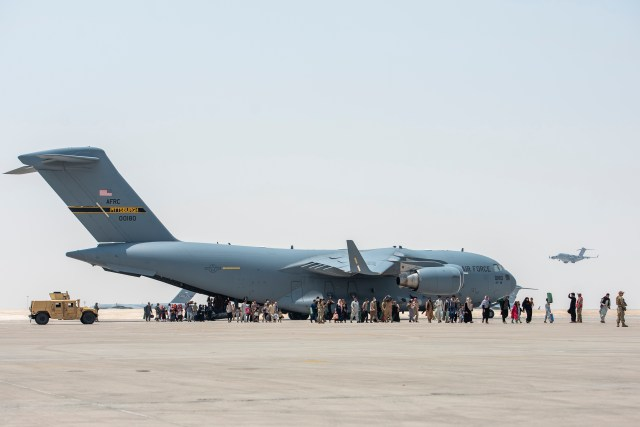 A C-17 Globemaster lll lands on the runway with evacuees from Afghanistan.