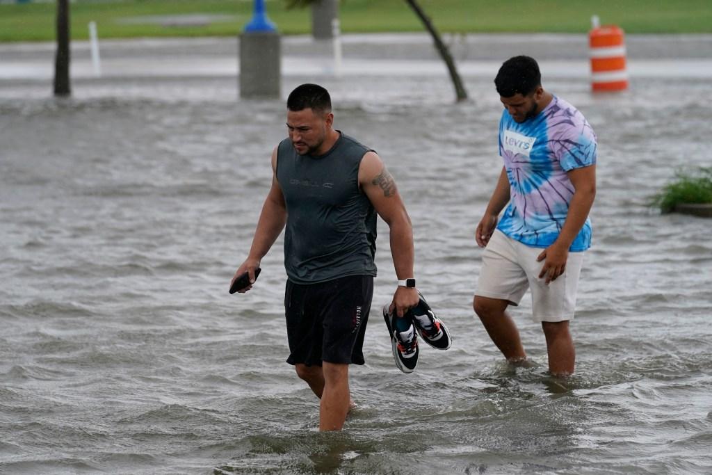 Jesse Perez, center, and Sergio Hijuelo walk through flooded streets near Lake Pontchartrain as Hurricane Ida nears, Sunday, Aug. 29, 2021, in New Orleans.